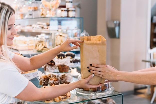 Shop assistant giving croissant bag Free Photo