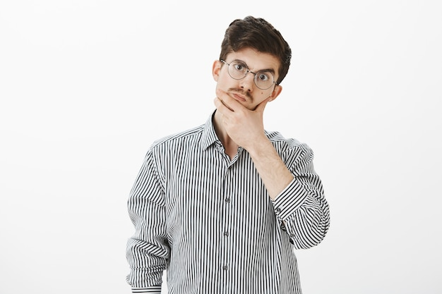 Shop assistant troubled to answer on question. confused unaware ordinary european guy in casual shirt and glasses, rubbing chin and lifting eyebrow, thinking and weighing chances on success Free Photo