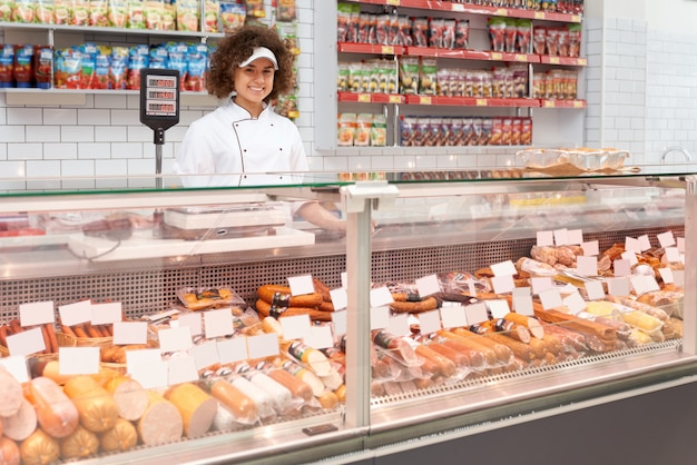 Operaio del negozio che posa dietro il contatore. Foto Gratuite