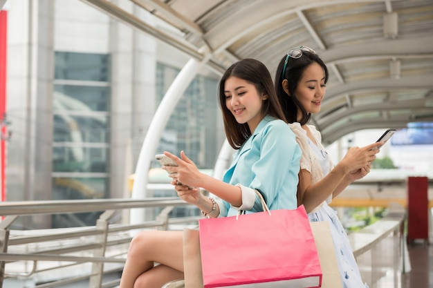 Shopaholic friends play smartphone in city Premium Photo