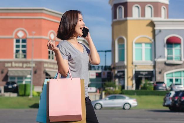 美しい若いshopaholicアジアの女性が話すためにスマートフォンを使用して 無料写真