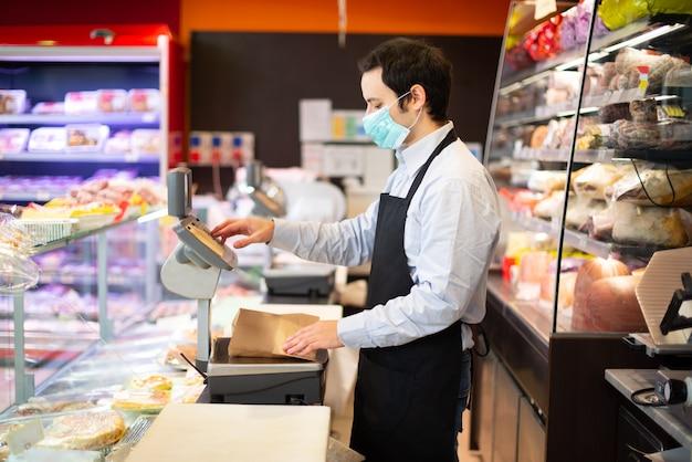 マスク、コロナウイルスのパンデミックの概念を着用しながらビジネスを実行する店主 Premium写真
