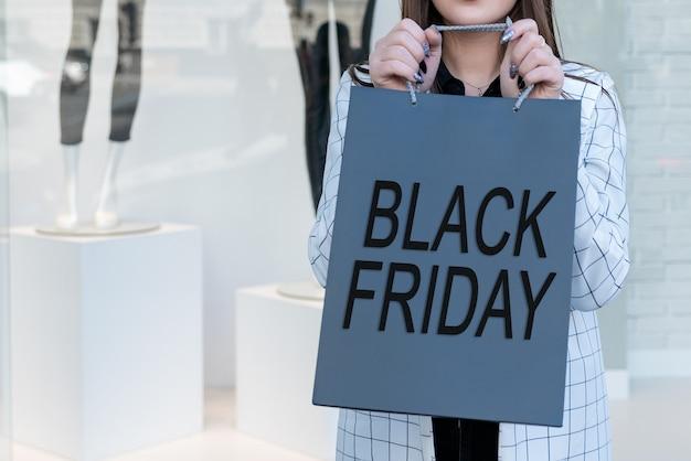 쇼핑몰에서 블랙 프라이데이 종이 봉지를 들고 쇼핑 프리미엄 사진