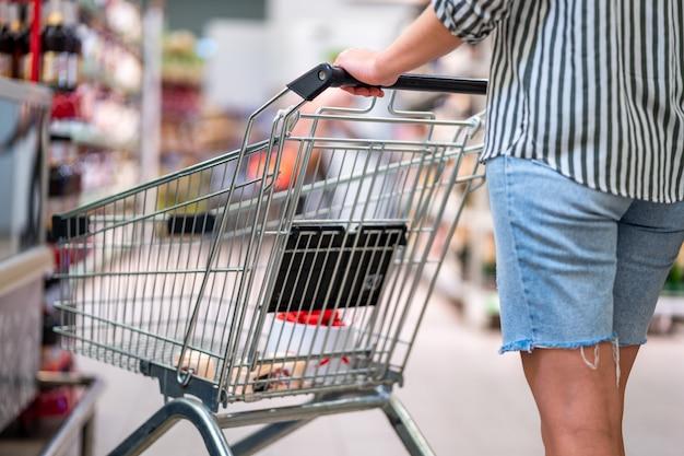 슈퍼마켓에서 쇼핑 카트 구매자. 식료품 점에서 음식을 구입. 식료품 쇼핑 프리미엄 사진