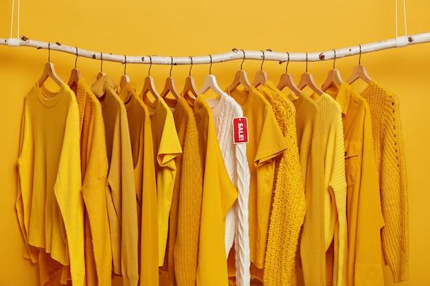 쇼핑 및 특별 제공 개념. 많은 노란색 옷 항목과 빨간색 태그 판매와 흰색 니트 스웨터. 무료 사진