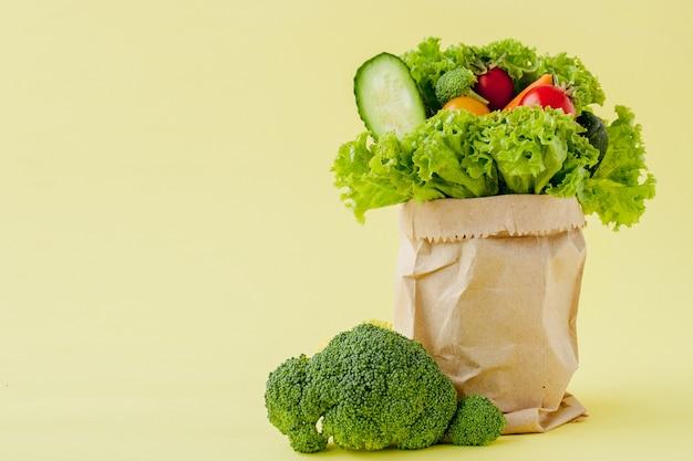 黄色の背景に食料品の買い物袋。 Premium写真
