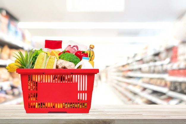 Shopping basket full of food and groceries on the table in supermarket Premium Photo