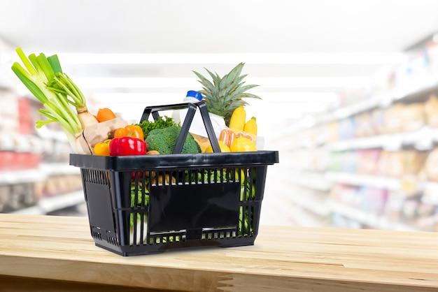 スーパーマーケットのバックグラウンドで木のカウンターで食料品の買い物かご Premium写真