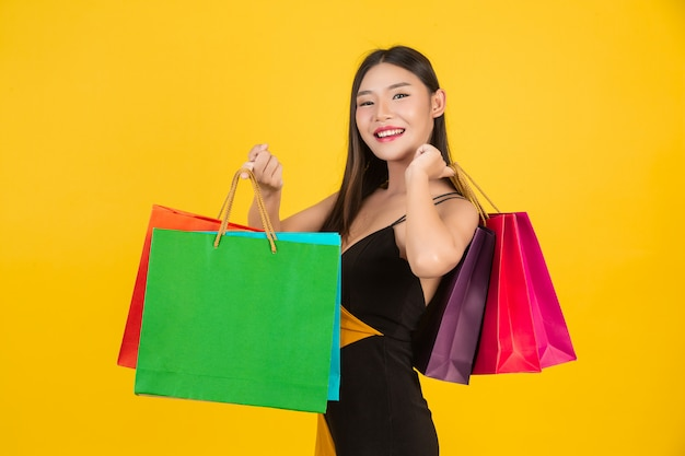 Shopping  beautiful woman holding a colorful paper bag on a yellow  . Free Photo