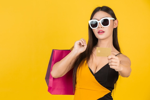 Shopping  beautiful woman wearing glasses with a gold credit card with a colorful paper bag on a yellow  . Free Photo