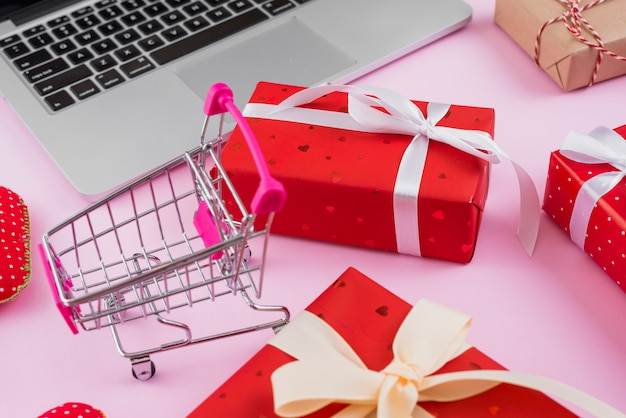 Shopping cart amidst gifts and modern laptop Free Photo