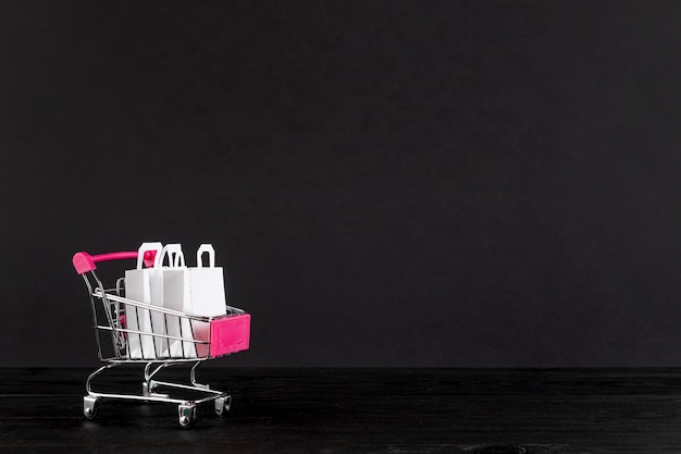 Shopping cart on black background with copy space Free Photo