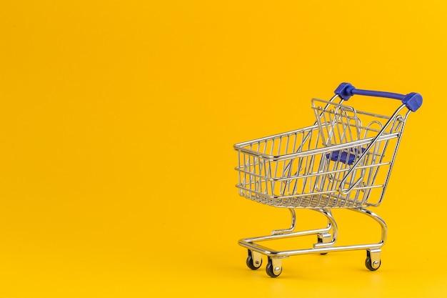 Shopping cart on bright yellow paper Premium Photo
