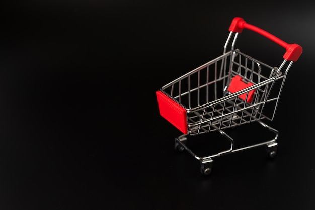Shopping cart on dark background with copy-space Free Photo