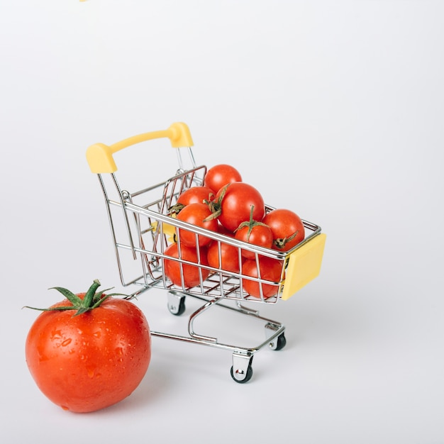 Shopping cart full of fresh red tomatoes on white backdrop Premium Photo