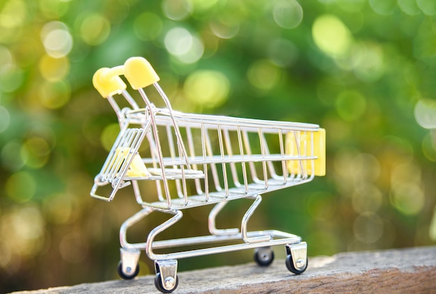Shopping cart on nature green bokeh background online shopping black friday concept with yellow shopping cart Premium Photo