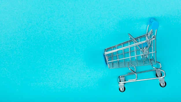 Shopping cart on plain background Free Photo