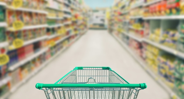 Shopping cart in supermarket and blurred photo store bokeh background Premium Photo