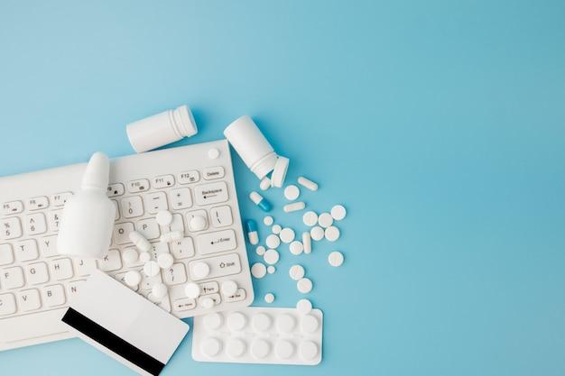 医薬品とキーボードを備えたショッピングカートのおもちゃ。錠剤、ブリスターパック、医療用ボトル、温度計、青色の背景に防護マスク。あなたのテキストのための場所のトップビュー Premium写真