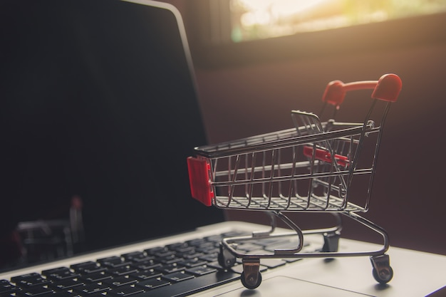 Shopping cart or trolley on a laptop keyboard. Premium Photo