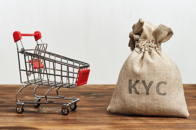 Корзина с сумкой денег и надписью kyc. Premium Фотографии