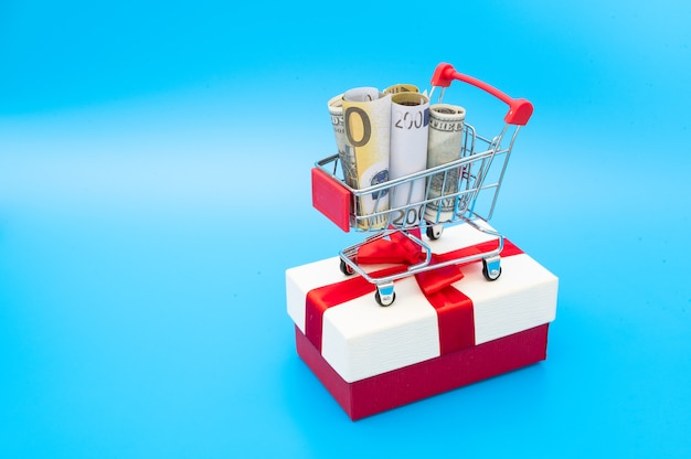 Shopping cart with american and european banknotes inside stand on gift box decorated with ribbon and bow Premium Photo