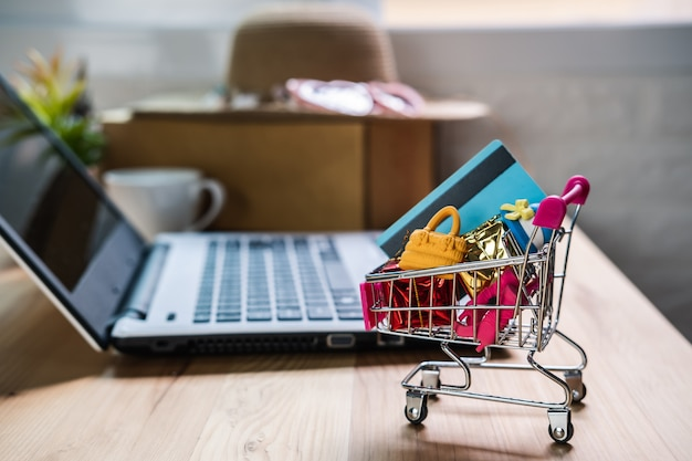 Shopping cart with credit card and woman accessories with laptop Premium Photo