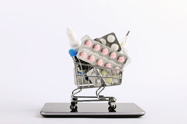 Shopping cart with drugs and pills is on the smartphone. online sales concept. Premium Photo