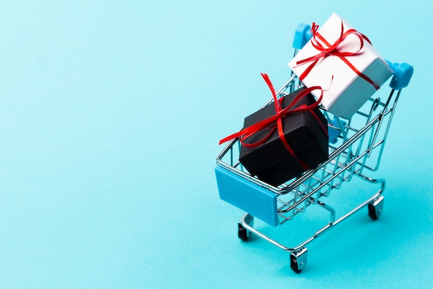 Shopping cart with gifts on plain background Free Photo