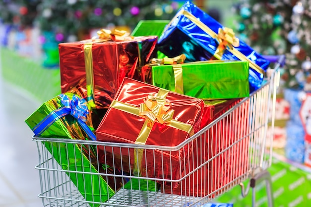 Shopping cart with gifts in supermarket background Premium Photo