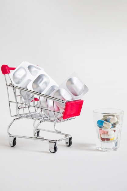 Shopping cart with pill blister and medicines in glass on white background Free Photo