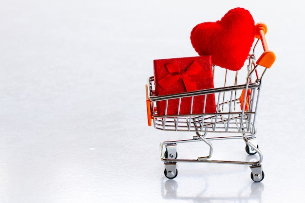 Shopping cart with red present box and confetti red hearts on a gray background copy space Premium Photo
