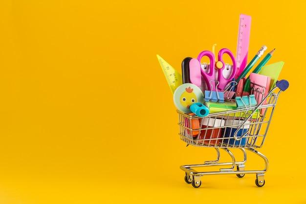Shopping cart with school supplies Premium Photo