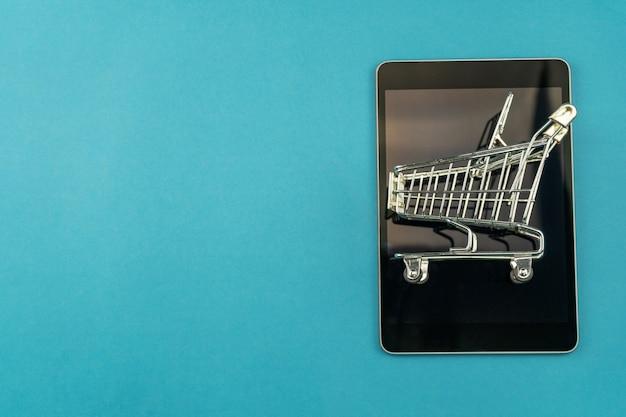 青色の背景、ビジネスショッピングオンラインコンセプトに分離されたタブレットでショッピングカート。 Premium写真