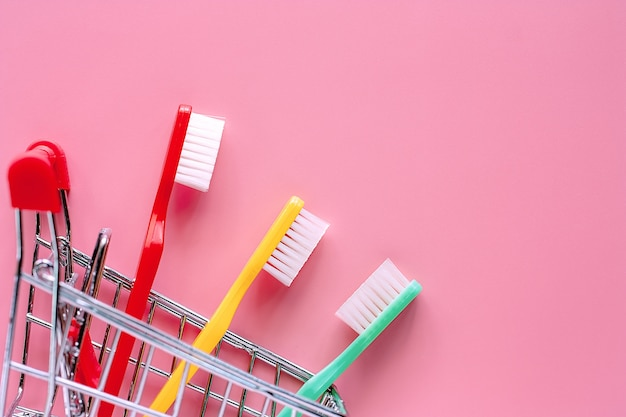 Shopping cart with toothbrush on pink background Premium Photo