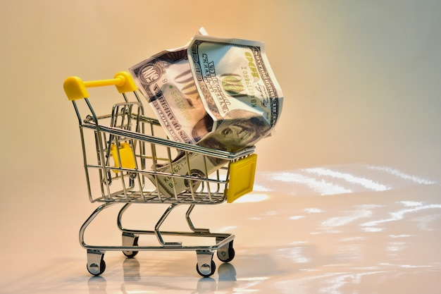 The shopping cart with yellow handle with dollar Premium Photo