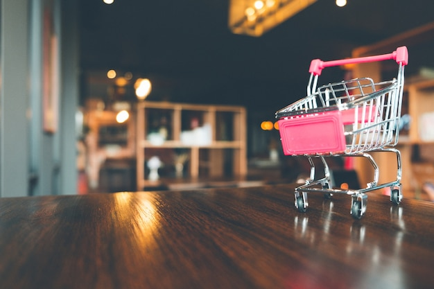 Shopping cart on wooden table in shop, online shopping and ecommerce concept. Premium Photo