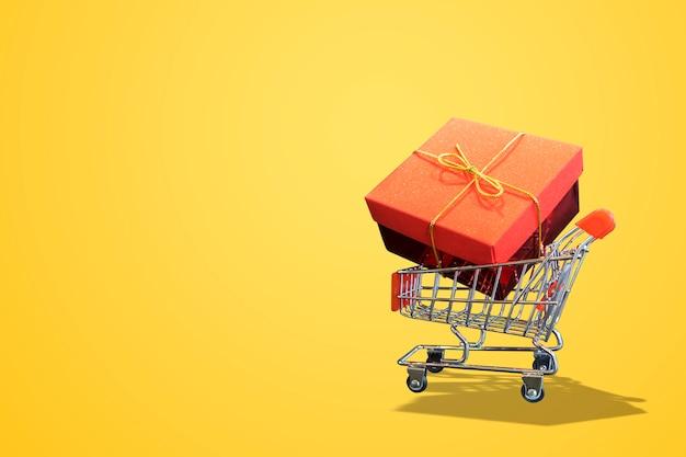 Shopping cart yellow background and gift box Premium Photo