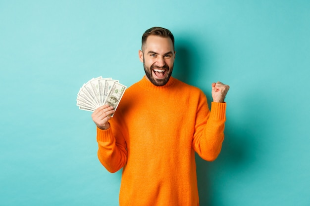 Shopping. cheerful guy holding money, winning prize in cash and making fist pump, triumphing Free Photo