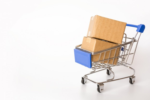 Shopping concept : cartons or paper boxes in blue shopping cart on white with copy space Premium Photo