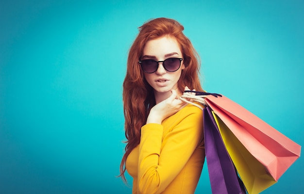 Shopping concept - close up portrait young beautiful attractive redhair girl smiling looking at camera with shopping bag. blue pastel background. copy space. Free Photo