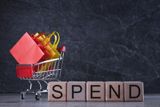 Shopping concept. wooden cubes with word spend cheap on dark table with shopping basket Premium Photo