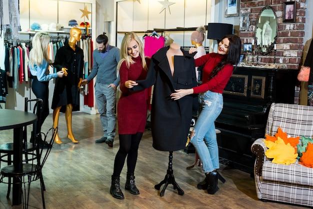 쇼핑, 패션, 옷, 스타일 및 사람들 개념-쇼핑몰이나 옷가게에서 코트를 입고 행복 친구 프리미엄 사진