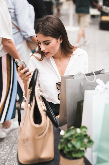 Shopping girl looking at her mobile phone Free Photo