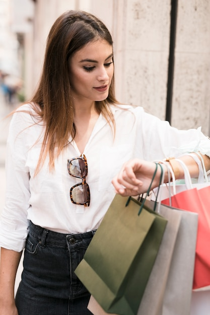 Shopping girl looking at her watch Free Photo