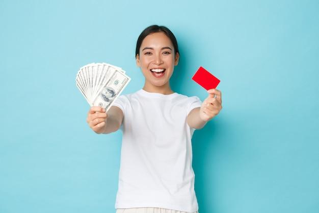 ショッピング、お金、金融の概念。誇り高い表情で現金とクレジットカードでドルを示し、水色の壁に満足して立っている幸せで喜んで笑顔のアジアの女の子。 無料写真