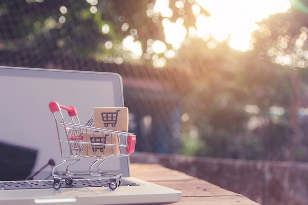 Shopping online concept - parcel or paper cartons with a shopping cart logo in a trolley on a laptop keyboard. shopping service on the online web. offers home delivery. Premium Photo