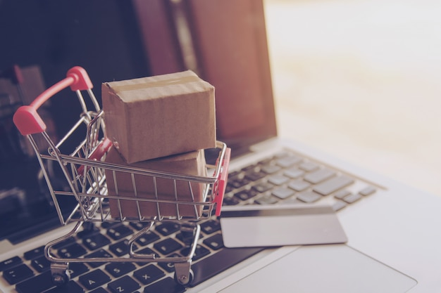Shopping online concept - shopping service on the online web. paper cartons with a shoppin Premium Photo
