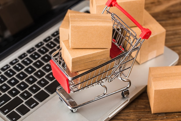 Shopping online at home conceptcartons in a shopping cart on a laptop keyboard Premium Photo