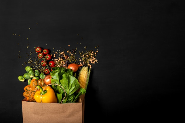 Shopping paper bag full of different fresh vegetables on a black background. purchases concept. healthy food organic selection. top view. copy space for text. Premium Photo